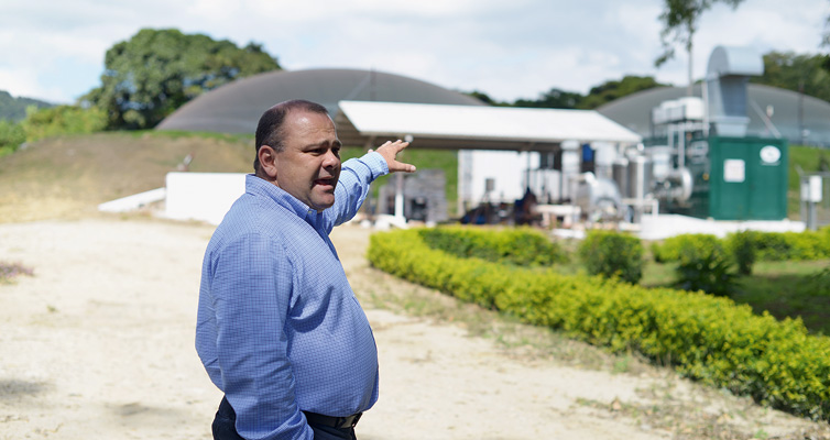 Happy entrepreneur: the biogas plant in the background generates clean energy for Saenz' business.