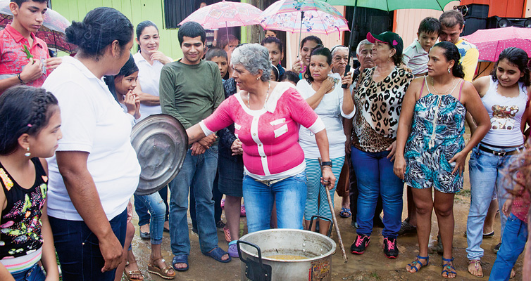 A hot meal: Urrego (beneath the green umbrella) and her neighbours enjoy a shared pot of stew.