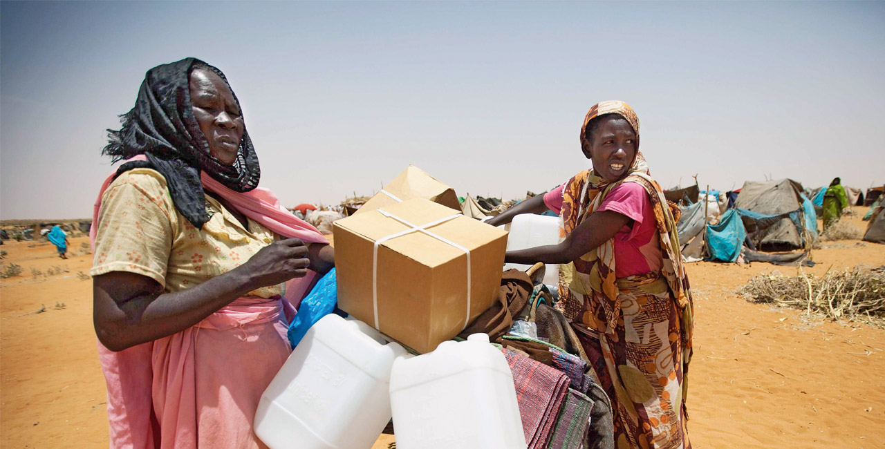 Women with aid supplies in a refugee camp in Darfur