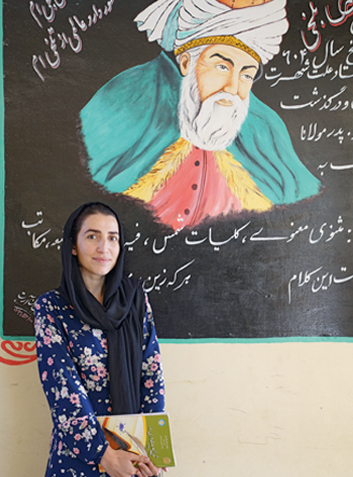 Literature scholar Deeda Shakeb in front of a painting of the icon of Afghan poetry: the national poet Rumi.  The 29-year-old works at  the Faizabad teacher training college.