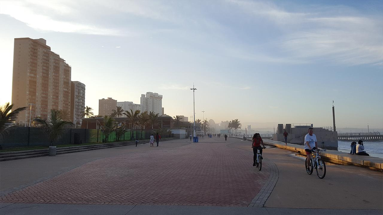 """Durban, Südafrika: Die Strandpromenade ist der ideale Ort, um sich zu entspannen. Die """"Goldene Meile"""", wie sie auch genannt wird, ist für jede*n zugänglich und gilt als sicherer öffentlicher Raum. Außerdem schützen die Mangrovenwälder und die Dünensanierung entlang der Promenade die Stadt vor Sturmfluten und dem Meeresspiegelanstieg.<br />© Lea Sarah Kulick"""