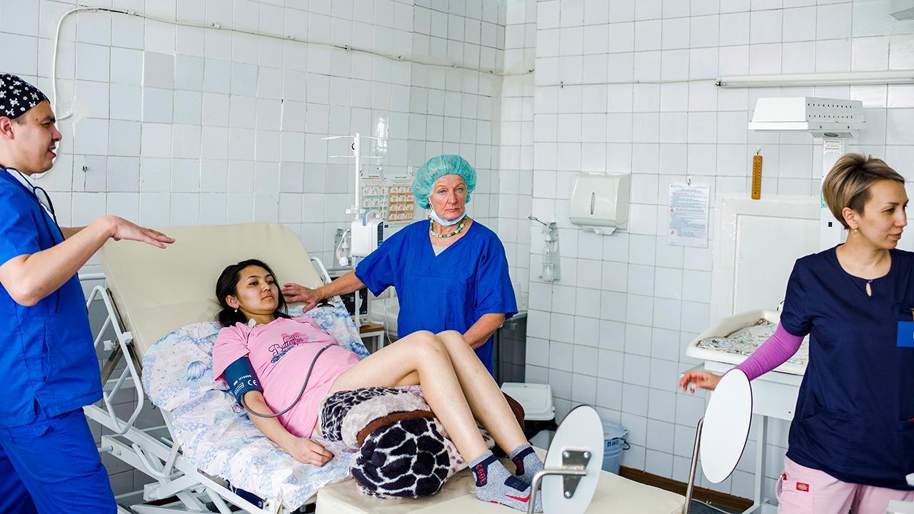 """Nachdem der Katheter fixiert ist, bleibt der Anästhesist noch mindestens 30 Minuten in engem Kontakt mit der Patientin. Erkontrolliert dabei regelmäßig, ob alles in Ordnung istoderungewöhnliche Symptome auftreten.<em> Foto: ©GIZ/Maxime Fossat</em><br />Mehr zu dem Projekt """"Perinatale Gesundheit in Kirgisistan"""" erfahren Sie unter <a href=""""https://giz-health.kg/en"""" target=""""_blank"""">https://giz-health.kg/en</a>"""
