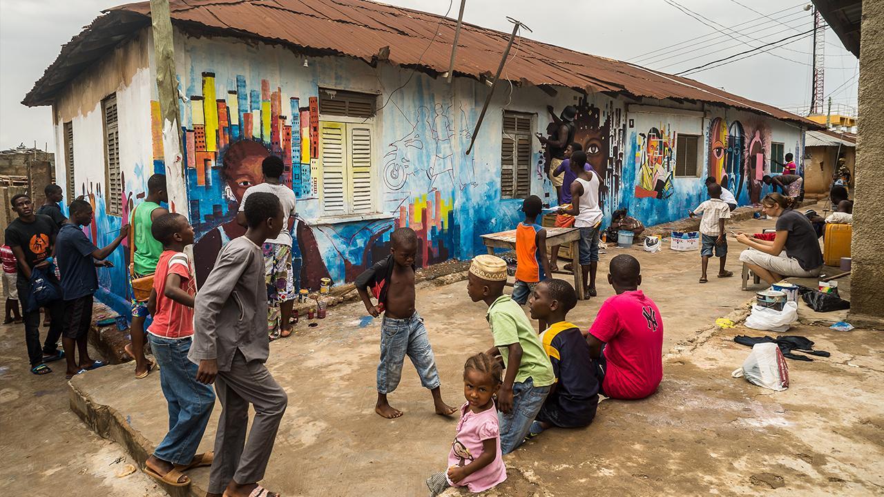 Accra, Ghana: Einheimische Künstler*innen verwandeln mit Kindern aus der Nachbarschaft alte Häuser in einzigartige Kunstwerke. Eine solche Aufwertung stärkt den sozialen Zusammenhalt innerhalb der Gemeinschaft und unterstützt die lokale Bindung.<br />© Lennard Kehl